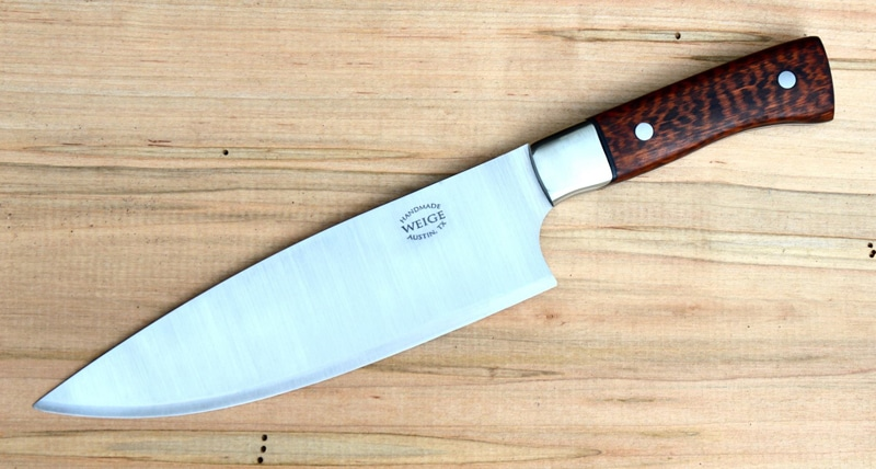 Custom chef in snakewood w/ stainless, dovetailed bolsters and nickel silver pins. Black vulcanized fiber liner.
