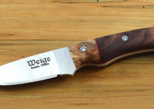 Custom drop point knife w/ a rosewood burl handle and maple bolster. Red liner and handmade paw print pins.