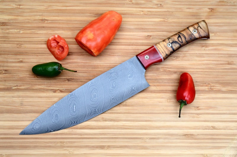 Custom damascus chef knife in TX pecan and red linen.