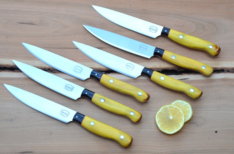 Set of 6 steak knives in osage orange w/ buffalo horn bolsters. Red vulcanized fiber liner.