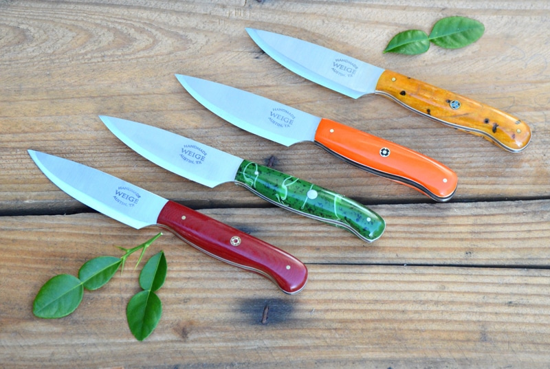 Set of paring knives in yellow box elder, orange G10, green kirinite and red linen.