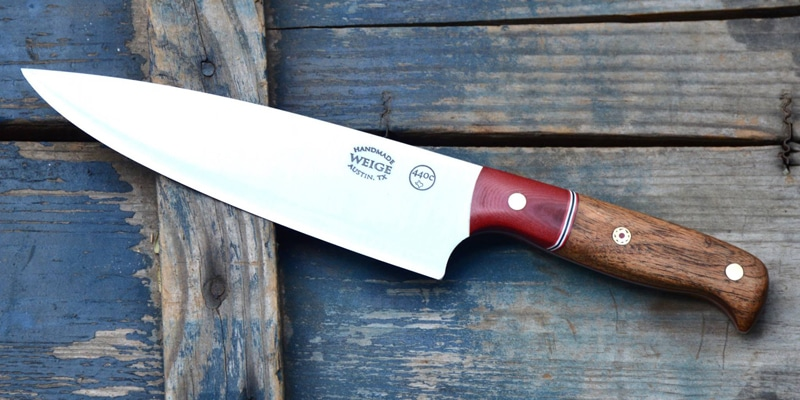 Custom chef knife in TX mesquite wood w/ a dovetailed red linen bolster. Stainless pins w/ a center handmade mosaic.
